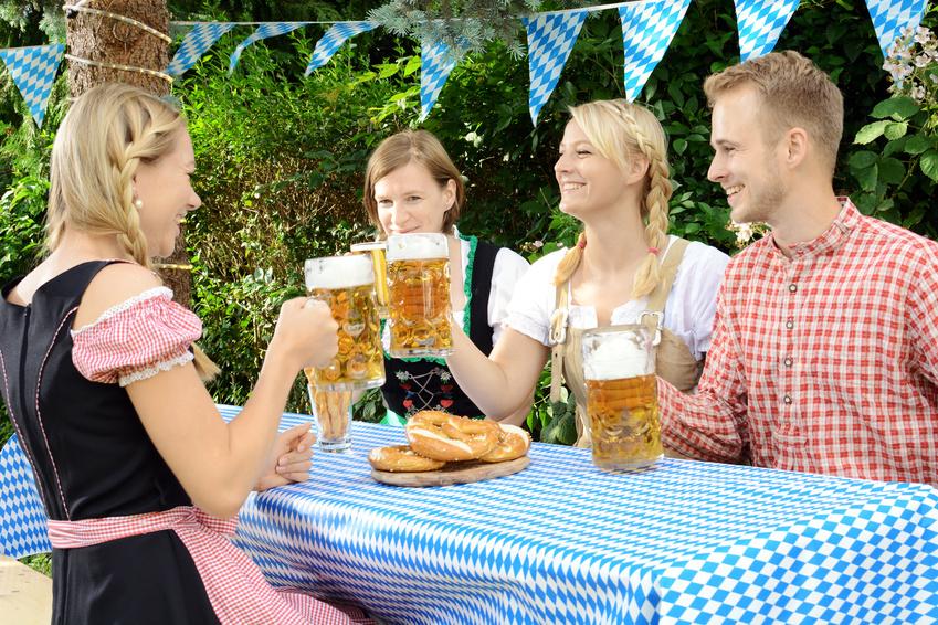 Freund im Biergarten stoßen mit Biermaß an
