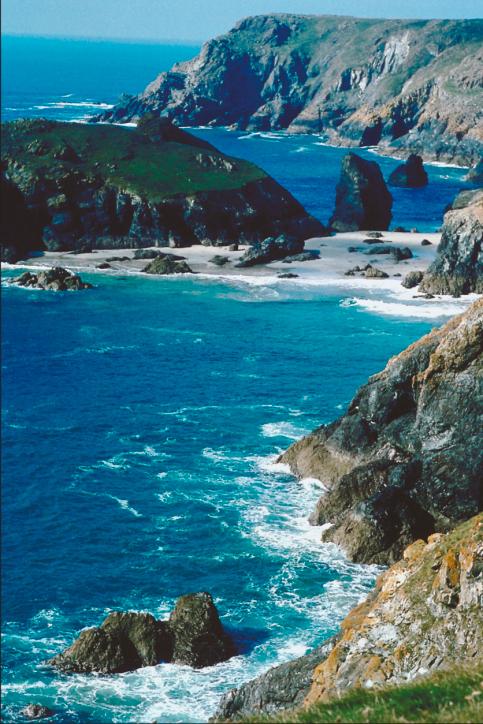 Von blauem Wasser umspülte raue Felsen an der Küste Cornwalls
